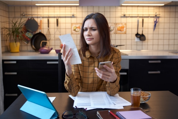 A woman sitting in her kitchen reviewing statements from creditors and debt collectors.