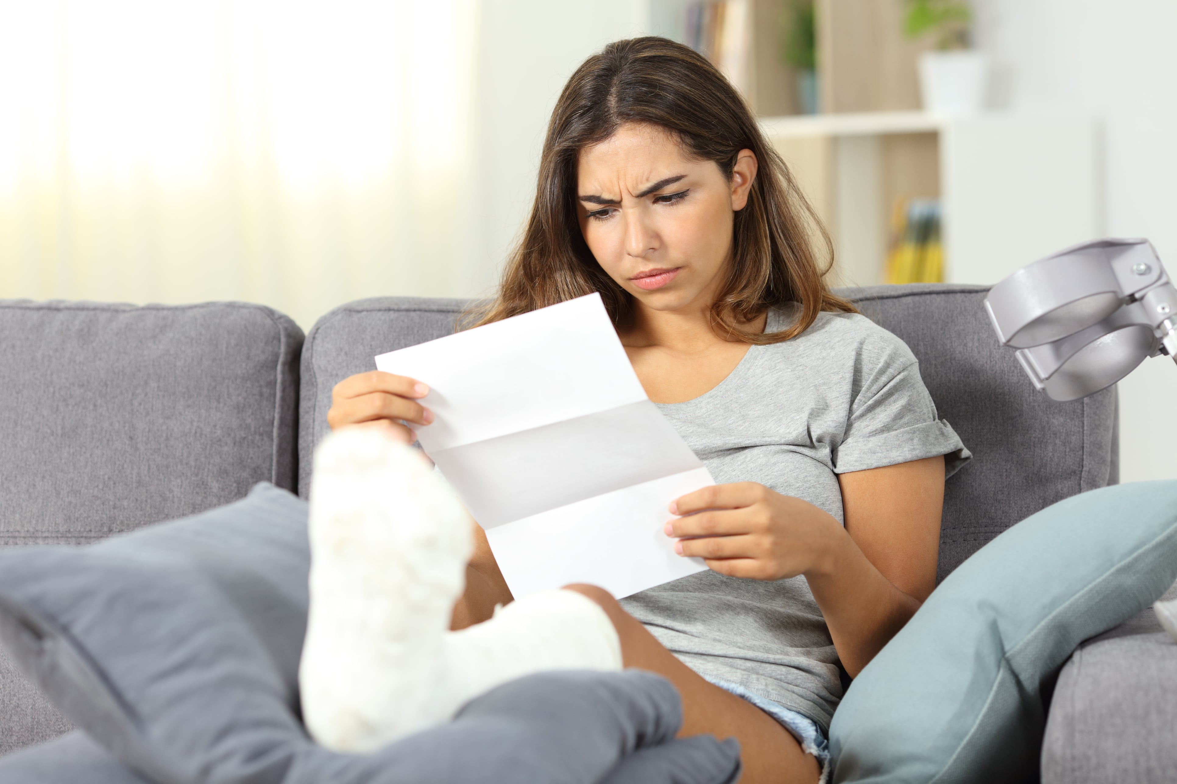 Woman with broken leg reviewing medical bills.