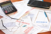 Unpaid bills on table leading to filing bankruptcy.