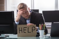 """Business man sitting at a desk considering filing bankruptcy holding a sign that reads """"help"""""""