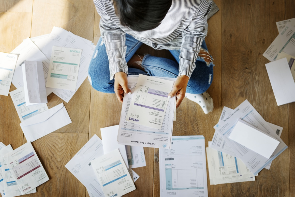 Woman sorting through bills on the floor and trying to pay off debt.