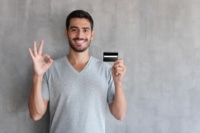 Picture of a man holding a credit card giving a thumbs up.