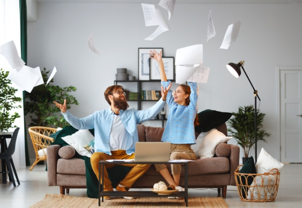 Excited couple throwing documents in the air after engaging in debt relief.
