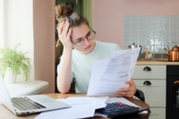 Young woman going through bills and considering debt consolidation.