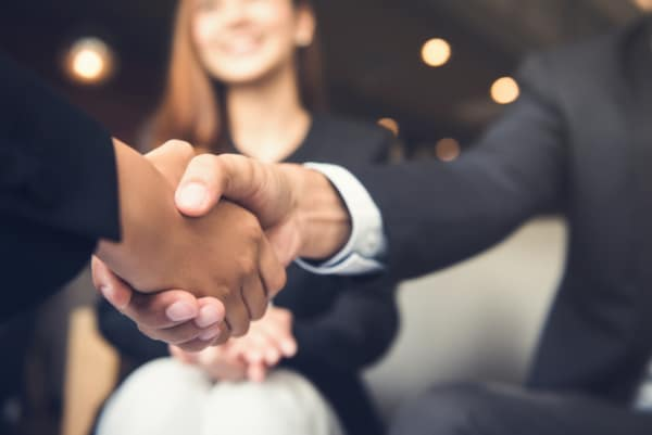 Couple shaking hands after receiving credit counseling.