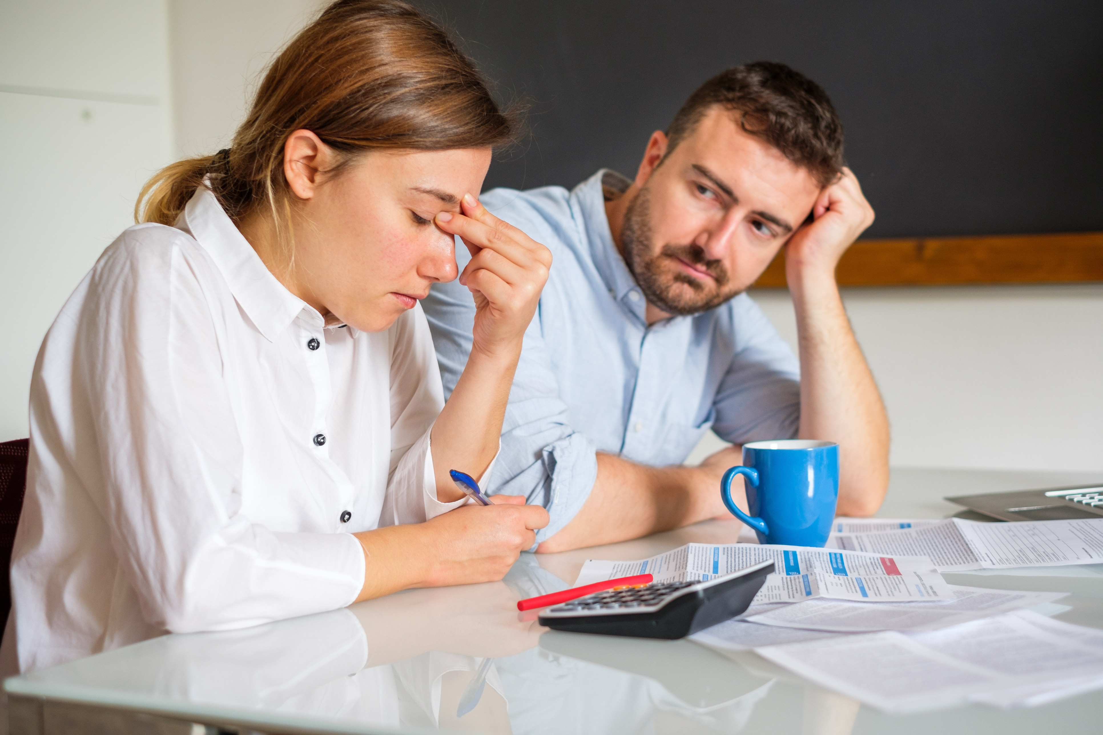 Stressed couple sitting at home and checking unpaid bills